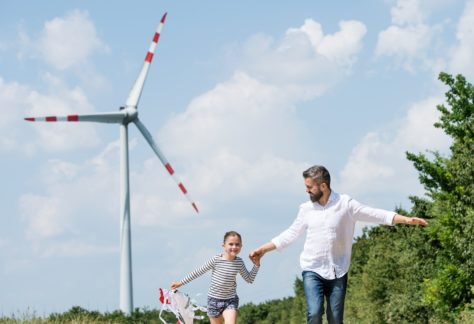 A mature father with small daughter on field on wind farm, running.