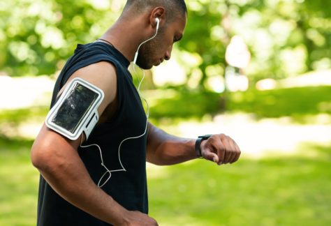 Side view of African American man checking health data on smartwatch after jogging at park